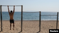 Мужчина делает упражнения на турнике на пустынном пляже в Афинах (Греция). 28 апреля 2020 года.