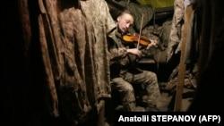 Український військовий грає на скрипці в бліндажі на передовій неподалік окупованої російськими гібридними силами Горлівки на Донеччині, 22 грудня 2020 року