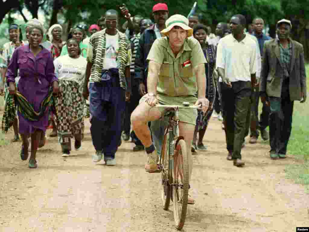 Zimbabwean commercial famer Tommy Bayley rides an old bicycle ahead of war veterans and villagers who invaded his farm Danbury Park 30 km's northwest of Harare to an abandoned house to use as temporary shelter April 8, 2000. Zimbabwe was thrown into turmoil in February when Mugabe's supporters and self-styled veterans of the 1970s war of liberation invaded white-owned farms, demanding land they said had been illegally taken away by colonisers. REUTERS