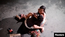 Филиппинка обнимает убитого в перестрелке мужа