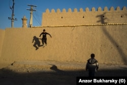 Boys play in the ancient center of Bukhara in March.