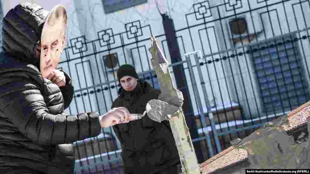 Активисты в масках президента России Владимира Путина и главы подконтрольного Кремлю правительства Крыма Сергея Аксенова «штукатурили» макет Ханского дворца.