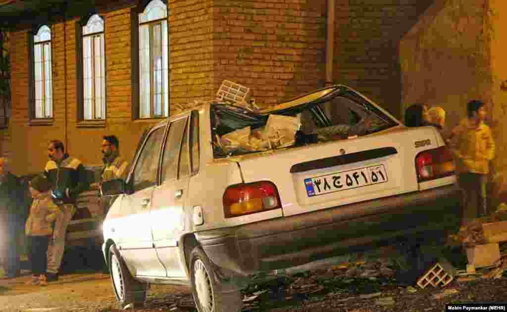 Поврежденный падающими обломками здания автомобиль.