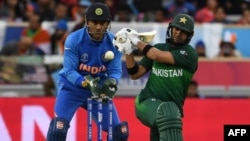 Pakistan's Rahat Ali (right) plays a shot watched by India's Mahendra Singh Dhoni during their Cricket World Cup group stage match in Manchester on June 16.