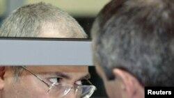 """Бывший глава """"ЮКОСа"""" Михаил Ходорковский в суде говорит с адвокатом. Москва, 15 апреля 2011 года."""