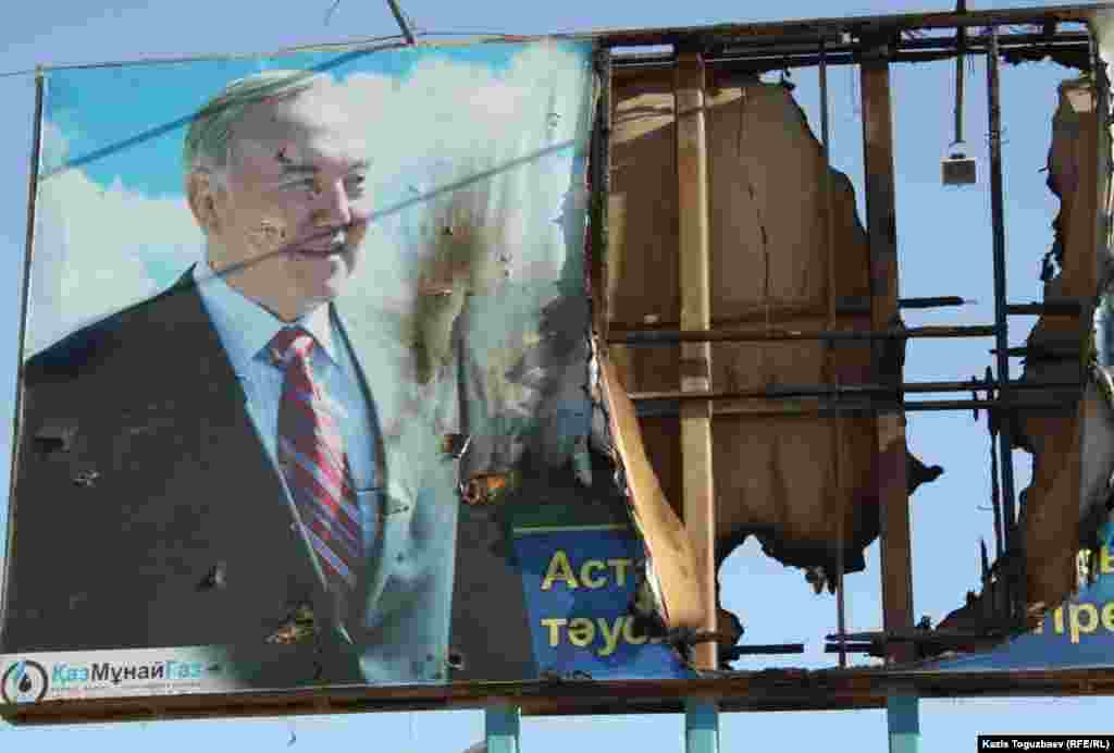 On the streets of Zhanaozen, a burnt-out banner featuring Kazakh President Nursultan Nazarbaev.