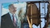Жартылай жанып кеткен президент Нұрсұлтан Назарбаевтың бейнесі басылған банер. Жаңаөзен, 19 желтоқсан 2011 жыл