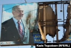 Поврежденный банер с изображением президента Нурсултана Назарбаева в городе Жанаозен. 19 декабря 2011 года.