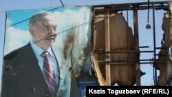 Нұрсұлтан Назарбаевтың суреті басылған жартылай өртенген билборд. Жаңаөзен, 19 желтоқсан 2011 жыл