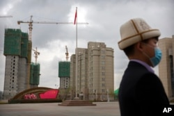 A man stands on a plaza near a display with the Chinese flag at the Xinjiang Islamic Institute in western China.