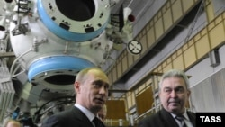 Russian then-Prime Minister Vladimir Putin (left) and Khrunichev Center chief Vladislav Nesterov confer at Khrunichev Space Center in March 2009.
