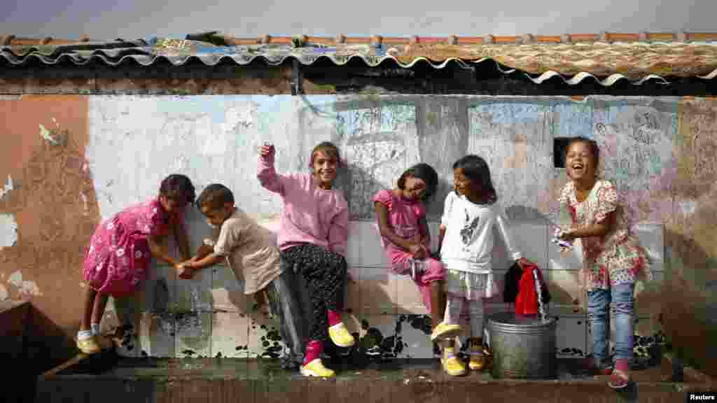 Romany refugees from Kosovo play in a water tap in Podgorica, Montenegro.