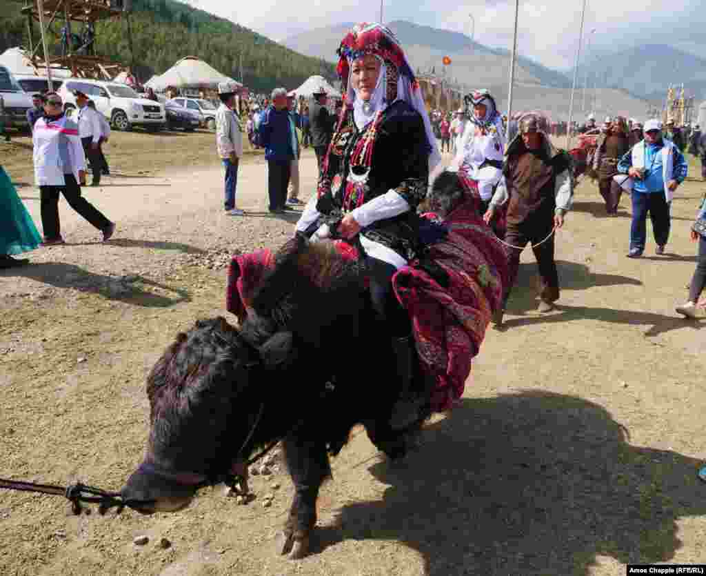 Elderly Kyrgyz women cruise through the crowds on yaks en route to the main stage.