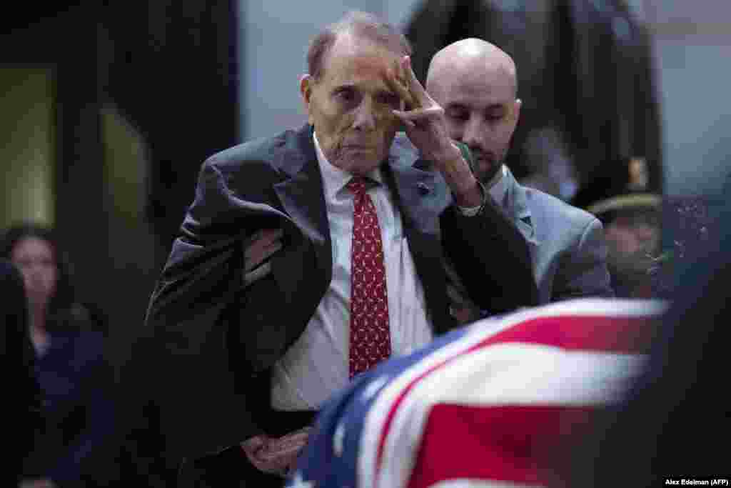Former U.S. Senator Bob Dole, a World War II veteran who is 95, asked an aide to help him stand up from his wheelchair to salute the flag-draped coffin of former U.S. President George Bush at the U.S. Capitol rotunda on December 4 in Washington. Bush, the 41st U.S. president, died on November 30 at the age of 94. (AFP/Alex Edelman / AFP)