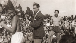 Photograph of Fredy Hirsch (right), organizer of fitness training, sports competitions, and summer activities for Prague's Jewish young people at Hagibor, 1930/40's. Edith Sheldon and Ada Löwy appear to be in the background behind Hirsch (left). Memory of Nations/Dita Krausová.