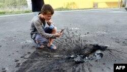 Соғыстан қалған шұңқырды суретке түсіріп отырған бала. Донецк, 22 шілде 2014 жыл.
