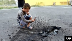 A young boy takes a picture of a crater left in the asphalt in the eastern city of Donetsk.