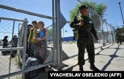 Кыргызский пограничник у ворот пограничного пункта пропуска на кыргызско-узбекской границе в Кара-Суу, примерно в 500 километрах к юго-востоку от Бишкека, 12 мая 2017 года.