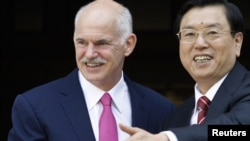 Greek Prime Minister George Papandreou (left) welcomes Chinese Vice Premier Zhang Dejiang to Athens on June 15.