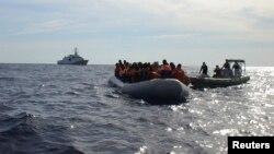 Итальянские военные подбирают мигрантов, переплывающих Средиземное море на небольшой лодке. 30 октября 2013 года.