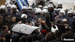 Anti-austerity protesters carry a police shield during scuffles in front of the parliament in Athens on February 7, when two of the largest Greek public sector unions went on a 24-hour strike.