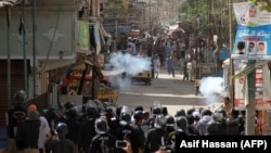 Pakistani policemen fire teargas shells towards protesters during a demonstration against the rape and murder of a six-year-old girl in Karachi on April 17.