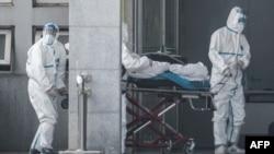Мэдыцынскія работнікі дастаўляюць пацыента ў лякарню, дзе атрымліваюць дапамогу пацыенты, інфікаваныя новым вірусам. Ухань, 18 студзеня 2020 году