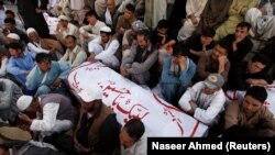 FILE: Shi'ite Muslim men from Pakistan's ethnic Hazara minority mourn around the coffins of their relatives, who were killed in a shooting attack, in Quetta in October 2017.
