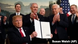President Donald Trump holds up a signed proclamation recognizing Israel's sovereignty over the Golan Heights, as Israeli Prime Minister Benjamin Netanyahu looks on in the Diplomatic Reception Room of the White House in Washington, Monday, March 25, 2019.