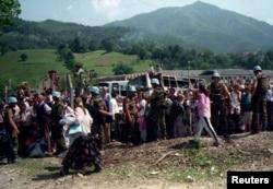 Dutch UN troops in Potocari stand alongside refugees from Srebrenica.