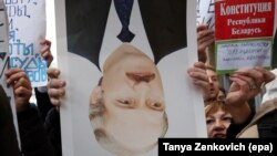 A protester holds a portrait of Belarusian President Alyaksandr Lukashenka upside down during a protest in Minsk.