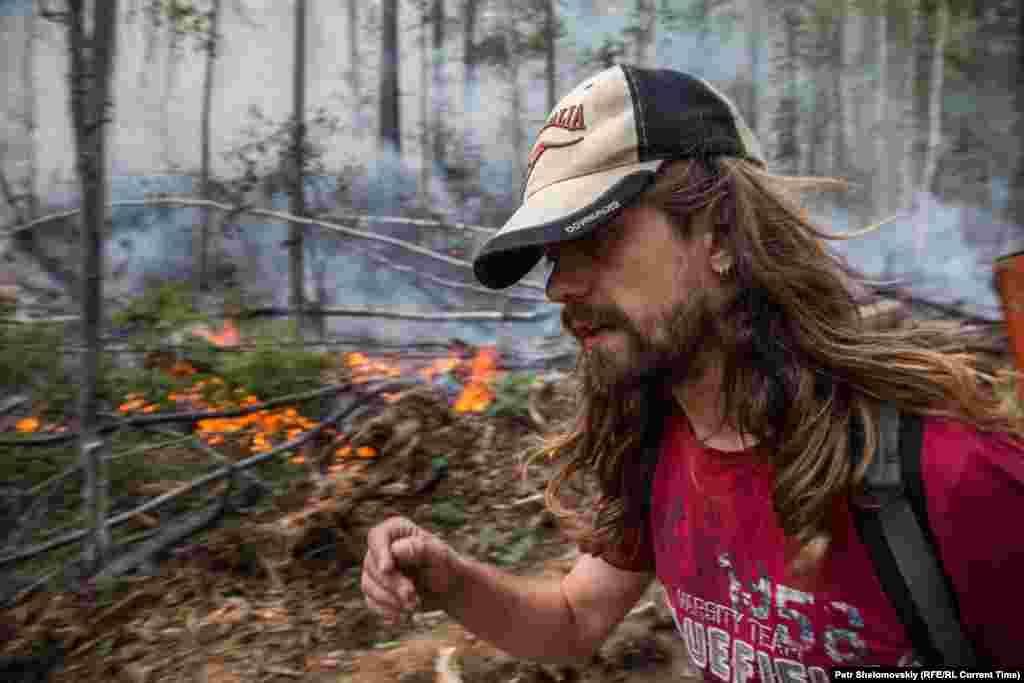 Volunteer Anton Volkov walks near a smoldering patch of fire.