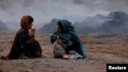 Пәкістанның Пешавар қаласында қоқыс тастайтын жерде отырған қыз балалар. (Көрнекі сурет.)