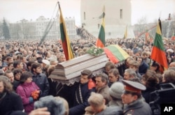 Huge crowds in Vilnius attend a funeral procession for 10 of the 14 people killed when Soviet troops stormed the Lithuanian broadcast center in January 1991.