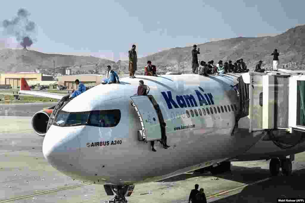 Афганистанци се качват върху самолет на летището в Кабул след внезапното превземане на столицата от талибаните и края на 20-годишната война.