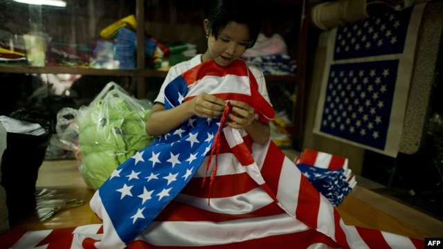 A woman folds U.S. national flags at a shop in Yangon, Burma, ahead of a visit by U.S. President Barack Obama.