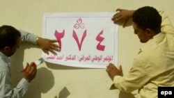 Iraqi men put up election posters on a street in Al-Najaf earlier this month.