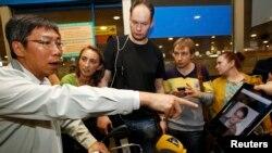 """Журналисты показывают фотографию Эдварда Сноудена пассажирам в аэропорту """"Шереметьево"""", пытаясь выяснить, был ли он на борту самолета. Москва, 23 июня 2013 года."""