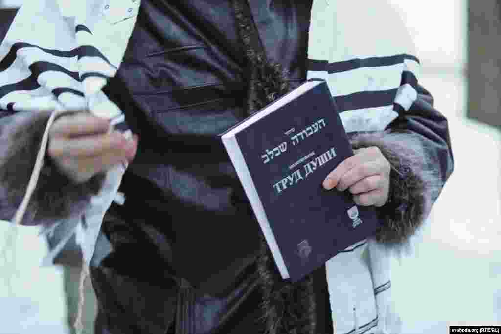 Молитвенник в руках участника акции памяти жертв Холокоста.