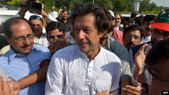 Pakistani cricketer-turned-politician Imran Khan (center) walks with supporters at a rally on the outskirts of Islamabad.