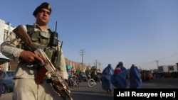 Afghan security official stands guard at a roadside checkpoint in Herat, Afghanistan, on August 3.