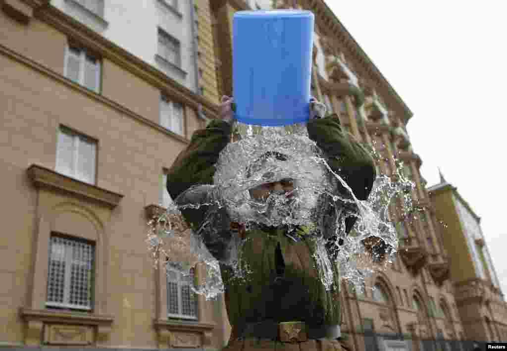 "Aleksei Didenko, a deputy in the Russian State Duma, dumps a bucket of cold water on himself in front of the American Embassy in Moscow. Didenko said he was performing the ice-bucket challenge not only to raise awareness for ALS but also to protest against the new U.S. Ambassador to Russia John Tefft and what Didenko called ""anti-Russian American propaganda."" (Reuters/Maxim Zmeyev)"