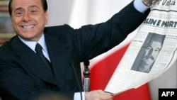 Italy's Prime Minister Silvio Berlusconi shows an old newspaper during his end-of-year news conference in Rome, 23 December 2005. Berlusconi blamed his political foes for an investigation by Italy's antitrust authority for alleged conflict of interest ove