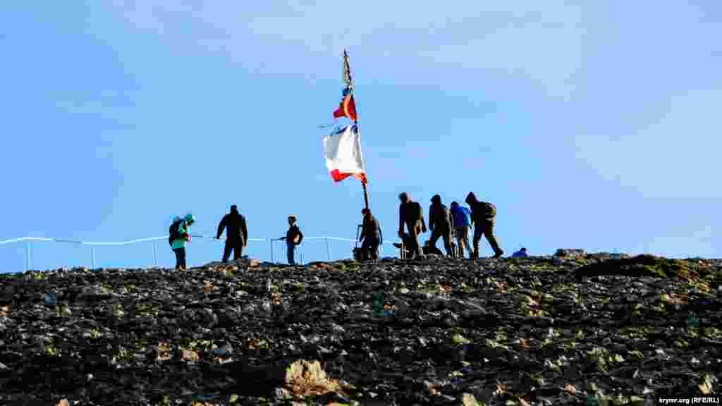 Туристы у самой высокой точки, на которой прикреплены флаги