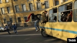 """Antigay protesters destroy a bus carrying gay activists during the """"Rainbow flashmob"""" organized in St. Petersburg on May 17."""