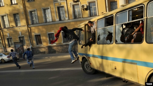 "Antigay protesters destroy a bus carrying gay activists during the ""Rainbow flashmob"" organized in St. Petersburg on May 17."