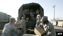 U.S. troops unload humanitarian aid at the air base in Manas on November 25.