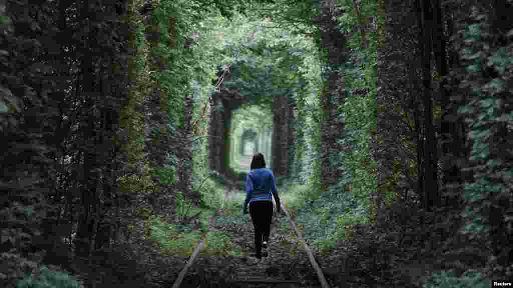 """A girl walks on a disused railway track, through what is known locally as the """"Tunnel of Love,"""" in the Ukrainian town of Kleven. (Reuters/Gleb Granich)"""