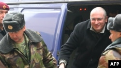 Russian police lead Mikhail Khodorkovsky out of a police van and into a Moscow court on March 4.