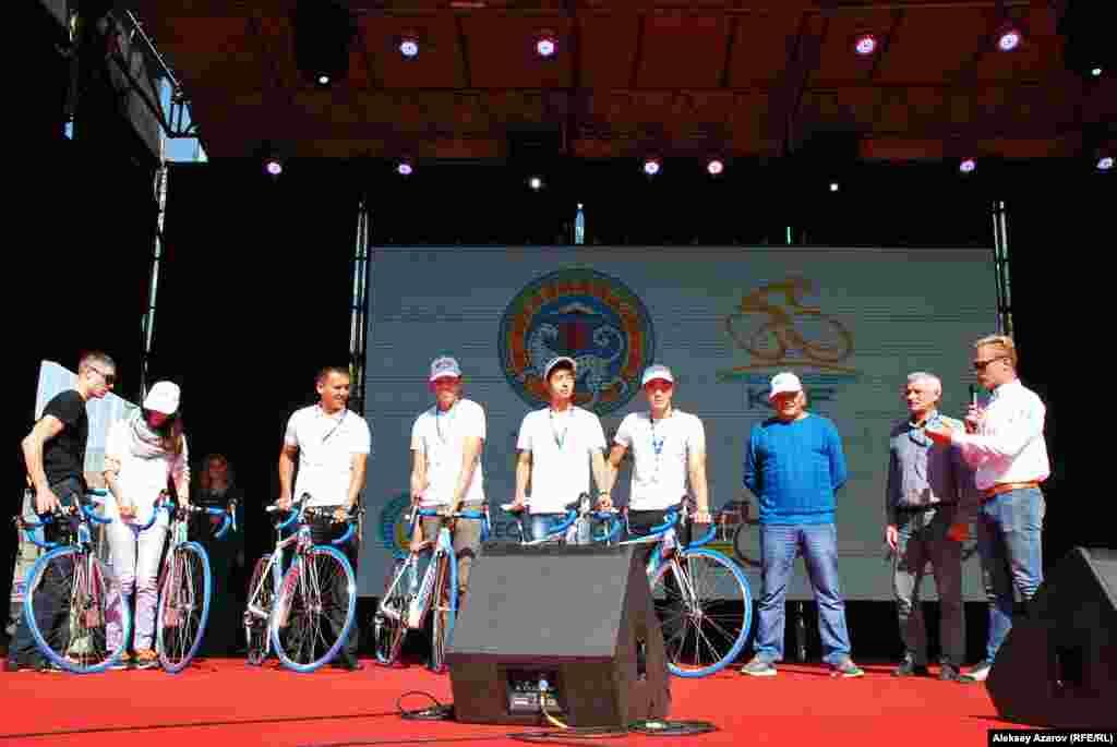 Пока продолжалась велогонка, руководитель фонда поддержки юных спортсменов имени Александра Винокурова Валентин Рехерт и сам Александр Винокуров (справа) награждали именными велосипедами Vino (по спортивному прозвищу Винокурова) победителей конкурса многодневных велогонок. Первое место заняла школа олимпийского резерва № 4 из Тараза. Приз - шесть именных велосипедов.